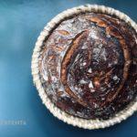 Zdjęcie przedstawia kosz na chleb wraz ze świeżo upieczonym chlebem.