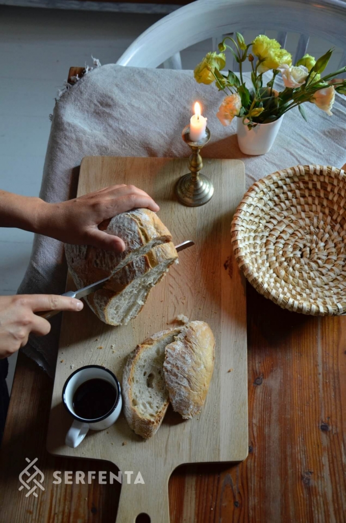 Zdjęcie przedstawia krojenie chleba.