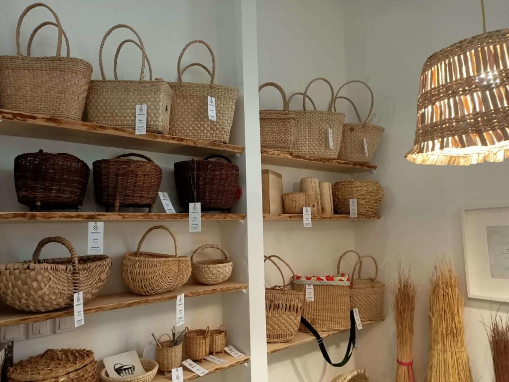 Półki na których prezentują się kosze z różnych materiałów - wiklina, słoma, torebki z rogożyny